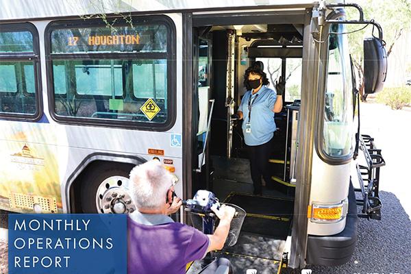 report cover driver wearing mask standing in bus doorway