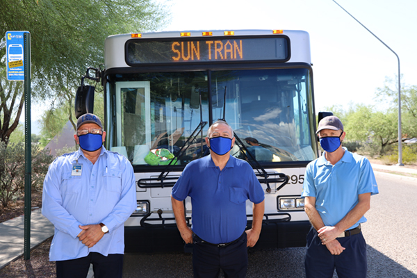 drivers standing in front of a bus